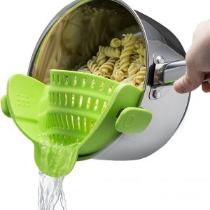 lime green strainer attached to a tilted pot straining pasta